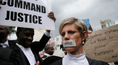 Zimbabwean lawyers carry placards as they march to demand justice for people